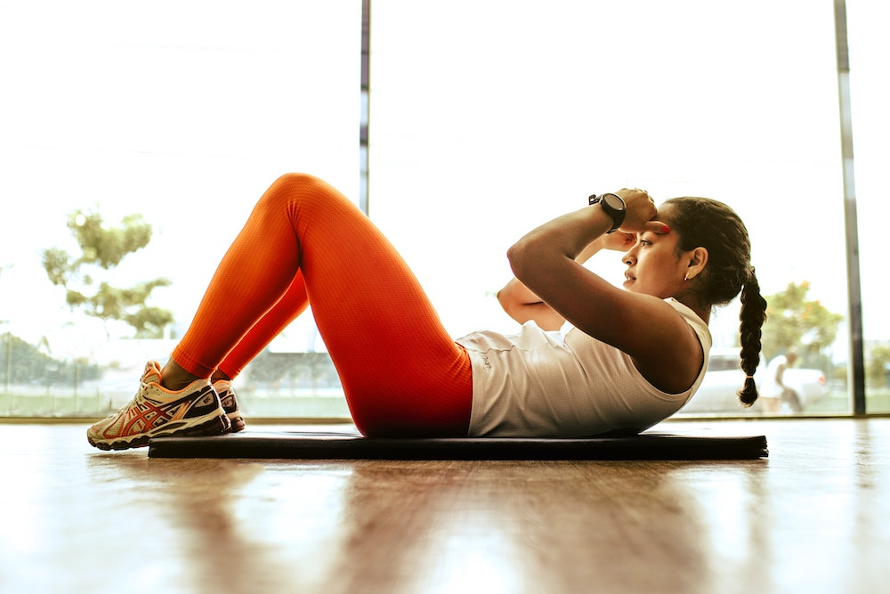 woman doing sit ups as part of healthy resolutions