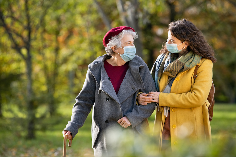 Lovely granddaughter walking with senior woman holding stick in park and wearing mask for safety against covid-19 - rapid covid-19 antibody test